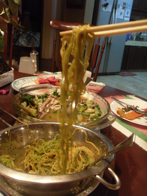 Sea weed noodles hanging by chopsticks